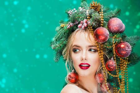 Portret van een mooie jonge vrouw met kerstboom in kapsel versierd met kralen en ballen op blauwe achtergrond. Vakantie make-up. Schoonheid, mode. Stockfoto