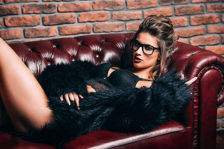 Seductive girl in the black lingerie and  fur jacket lying on a leather sofa. Luxurious lifestyle. Fashion, beauty. Studio shot. Stock Photo