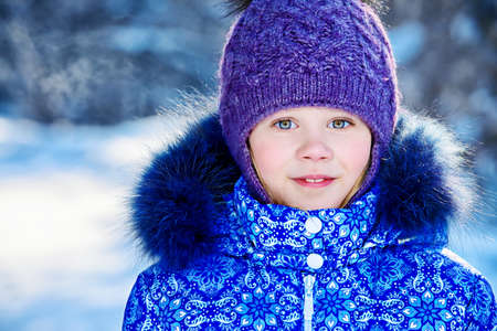 Joyful child girl playing outdoor on a sunny winter day. Winter clothes for kids. Archivio Fotografico
