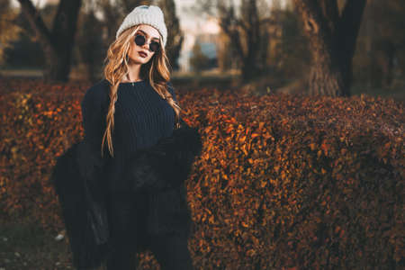 Autumn fashion shot. Trendy young woman in warm clothes posing in the autumn park. Youth style.