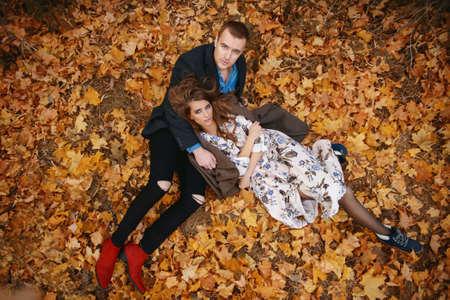 秋のファッション。黄ばんだ秋の草や葉の上に横たわる美しいファッショナブルなカップル。 写真素材