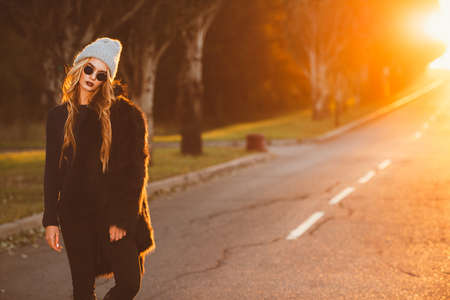 Autumn fashion shot. Trendy young woman in warm clothes posing on a highway on a sunset. Youth style.