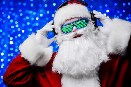 DJ Santa Claus in luminous glasses and headphones. Christmas songs and music. Disco lights in the background.