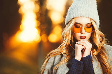 Autumn fashion. Fashionable young woman wearing warm sweater, a coat and a woolen hat posing in the park at a sunset. Archivio Fotografico