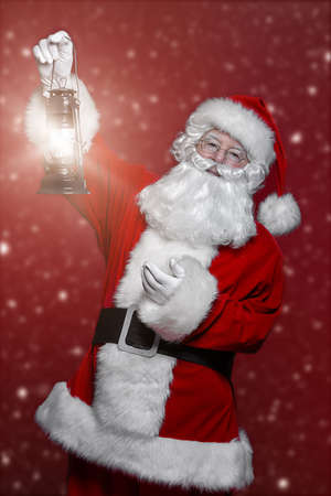 Christmas concept. Portrait of a fairytale Santa Claus holding lantern over red background. Magic time. Copy space.