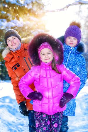 Glückliche Kinder, die zusammen im Freien an einem sonnigen Wintertag spielen. Schneefall. Winterkleidung. Winter Aktivität. Standard-Bild