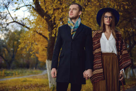Portrait of a beautiful young people walking in the autumn park. Autumn fashion.  Stock Photo
