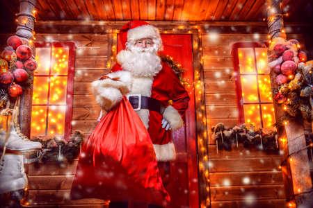 良い古いサンタ クロースの彼の装飾家のベランダにプレゼントの袋を保持の肖像画。サンタ クロースの家です。クリスマスと新年のコンセプトです