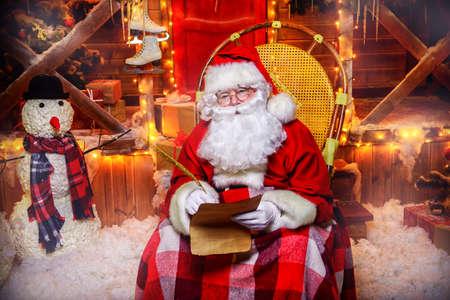 サンタ クロースは、クリスマスの準備です。彼は手紙を書いています。サンタ クロースの家です。クリスマス装飾。 写真素材