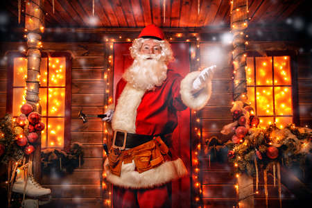 Santa Claus is a builder. House of Santa Claus. Portrait of Santa Claus with tools in his hands and a helmet on his head standing near his decorated house. Christmas and New Year concept.