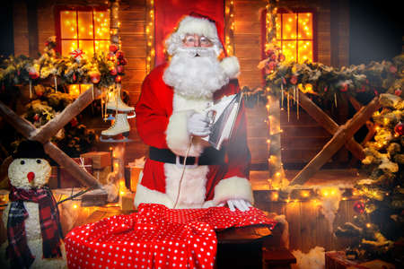 Santa Claus is ironing clothes in the courtyard of his house. House of Santa Claus. Christmas and New Year concept.