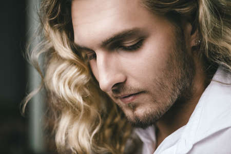 Close-up portrait of a handsome young man with long curly blond hair. Men's beauty, health. Skincare, cosmetics. 스톡 콘텐츠