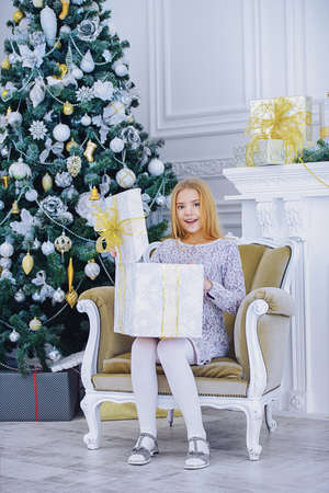 Pretty nine year old girl opens a gift box and surprises. Luxurious apartments decorated for Christmas. Merry Christmas and Happy New Year. Banque d'images