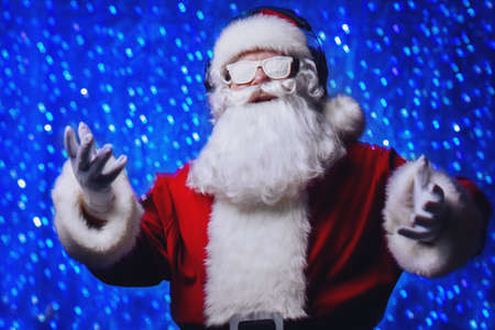 DJ Santa Claus in snowy glasses and headphones. Christmas songs and music. Disco lights in the background.