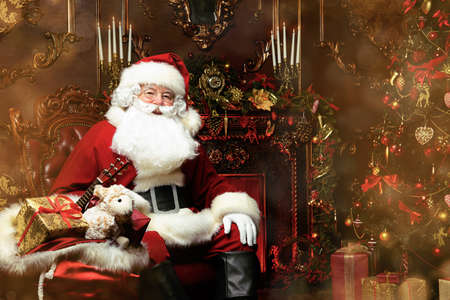 Surprised Santa Claus in a beautiful room next to the fireplace and Christmas tree sits with a sack of gifts .