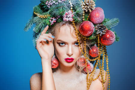 Portrait of a beautiful young woman with christmas tree in hairstyle decorated with beads and balls over blue background. Holiday make-up. Beauty, fashion.
