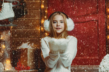 Pretty child girl is standing near her house decorated for Christmas with snow in her palms. Merry Christmas and Happy New Year. Stockfoto