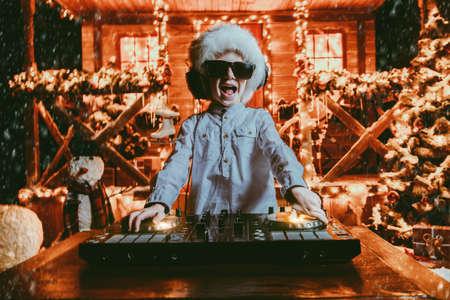 Emotionaler kleiner Junge-DJ hat eine Party nahe dem Haus des Weihnachtsmannes, der mit Lichtern verziert wird. Weihnachtsfeier-Konzept. Standard-Bild - 91446322
