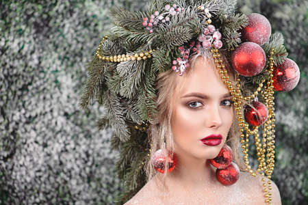Close-up portrait of a beautiful young woman with christmas tree in hairstyle and holiday make-up over snow-covered green background. Beauty, fashion. 写真素材