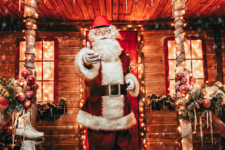 Santa Claus is a builder. House of Santa Claus. Portrait of Santa Claus in a helmet on his head standing near his decorated house and shows the thumb. Christmas and New Year concept. Banco de Imagens