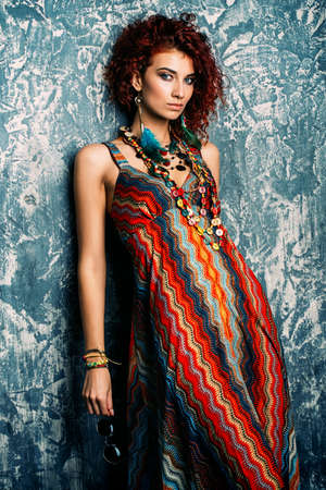 Beautiful bright woman with curly foxy hair wears a dress and beads in boho style. Ethnic style in clothes. Reklamní fotografie