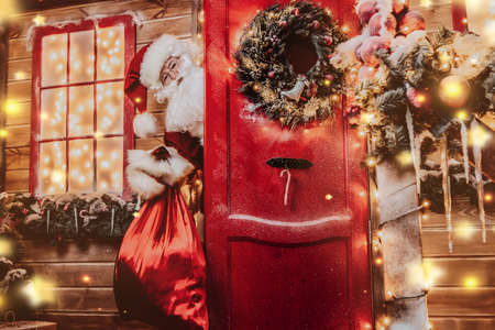 Christmas concept. Portrait of a fairytale Santa Claus peek out from behind the door with a bag of gifts in hands. Beautiful house decorated for Christmas. Time of miracles.