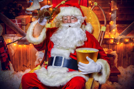 Santa Claus sitting on his armchair eating popcorn, looking through binoculars. House of Santa Claus. Christmas decoration.  Merry Christmas and Happy New Year. Stock Photo
