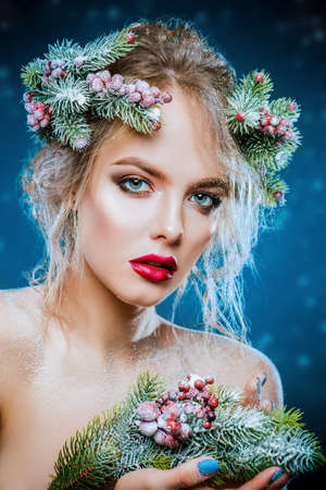 Portrait of a beautiful young woman with christmas tree in hairstyle and holiday make-up. Beauty, fashion.