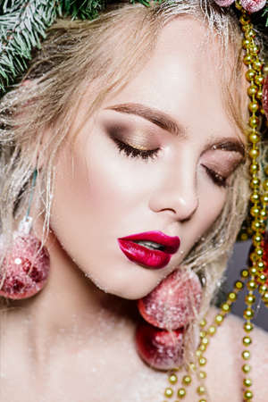 Close-up portrait of a beautiful young woman with christmas balls earrings. Holiday makeup. Beauty, fashion. Jewelry.