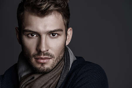 Close-up portrait of a handsome young man with brave manly face. Male beauty, cosmetics. Imagens