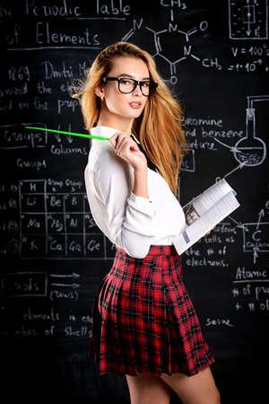 학교 유니폼 및 칠판 배경 위에 안경 포즈 긴 금발 머리 가진 귀여운 학생 소녀. 스톡 콘텐츠