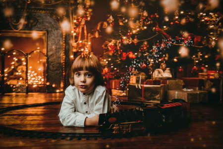 Cute five-year-old boy playing with a toy railway near the Christmas tree. Christmas night. Christmas decoration. Stock Photo