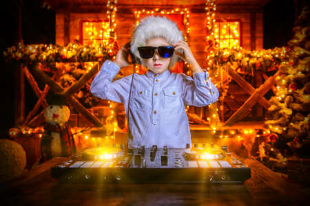 Little boy-DJ is having a party near the house of Santa Claus decorated with lights. Christmas party concept.