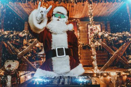 DJ Santa Claus in leuchtenden Gläsern und Kopfhörern veranstaltet eine Party in der Nähe seines mit Lichtern geschmückten Hauses. Weihnachtslieder und Musik. Standard-Bild