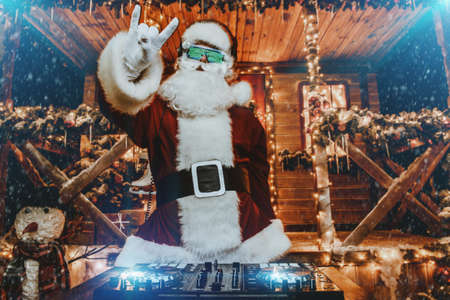 DJ Santa Claus in luminous glasses and headphones holds a party near his house decorated with lights. Christmas songs and music. Reklamní fotografie - 91609545