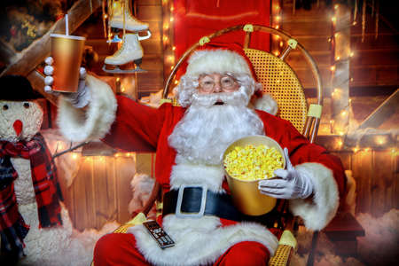 Santa Claus sitting on his armchair eating popcorn, drinking soda and watching a Christmas movie. Entertainment and cinema concept. Merry Christmas and Happy New Year. Zdjęcie Seryjne