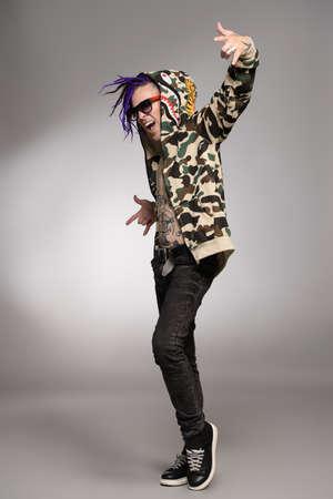 Punk rock musician posing at studio. Youth alternative culture. Full length portrait. 스톡 콘텐츠