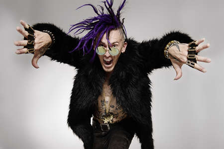 Portrait of a punk rock musician posing at studio. Youth alternative culture.