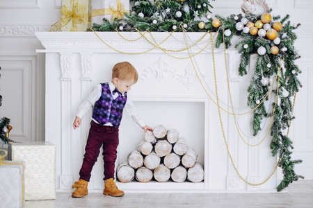 Cute three-year-old boy in elegant evening clothes poses in a beautiful room near fireplace decorated for Christmas. Luxurious apartments decorated for Christmas. Merry Christmas and Happy New Year. Stock Photo