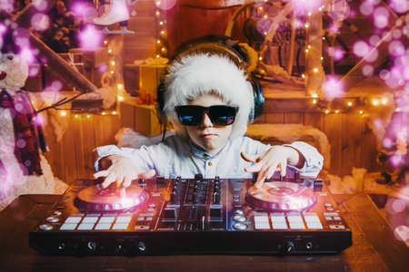 Emotional little boy-DJ is having a party near the house of Santa Claus decorated with lights. Christmas party concept.