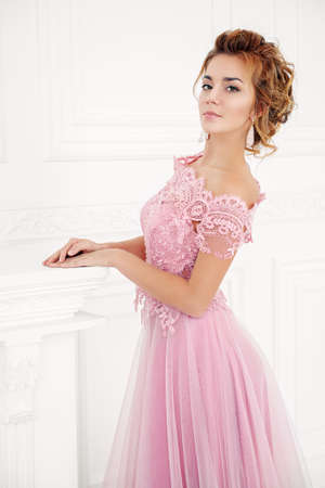 Elegant young woman in a luxurious evening dress posing a white vintage room. Wedding fashion. Evening fashion.
