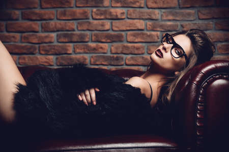 Seductive girl in the black lingerie and  fur jacket lying on a leather sofa. Luxurious lifestyle. Fashion, beauty. Studio shot. Banque d'images