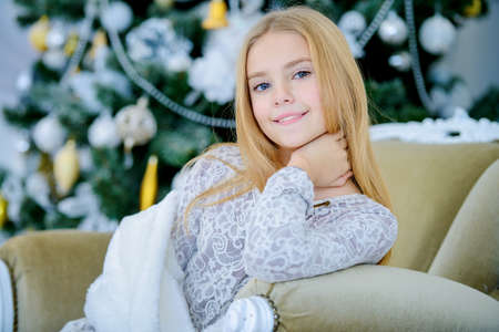 Pretty smiling girl sitting in a armchair in a Christmas room. Merry Christmas and Happy New Year. Stock Photo