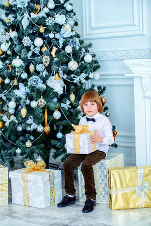 Cute Five-year-old Boy Sits In A Beautiful Room Near A Christmas ...