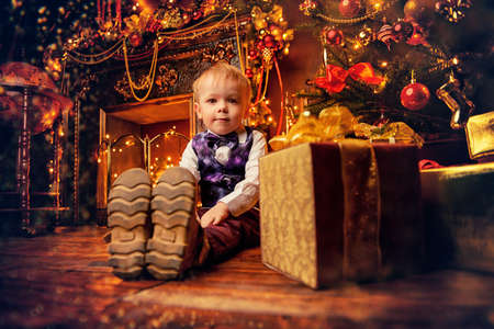 Cute three-year-old boy sits near the Christmas tree. Christmas night. Christmas decoration.