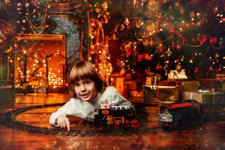 クリスマスツリーの近くでおもちゃの鉄道で遊ぶかわいい5歳の男の子。クリスマスの夜クリスマスの飾り 写真素材