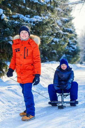 Zwei glückliche Jungen, die von einem Hügel an einem sonnigen Wintertag rodeln. Schnee. Winterkleidung. Winter Aktivität. Standard-Bild