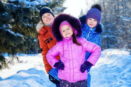 Happy children playing together outdoor on a sunny winter day. Snowfall. Winter clothes. Winter activity.