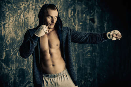 Handsome athletic man in hoodie stands by a grunge wall. Boxer, street fighter.  Stock Photo