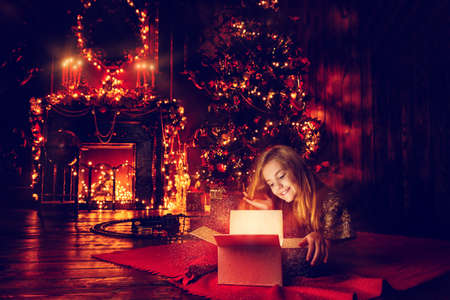 Pretty nine year old girl opens a gift box and surprises. Luxurious apartments decorated for Christmas. Merry Christmas and Happy New Year. Stock Photo